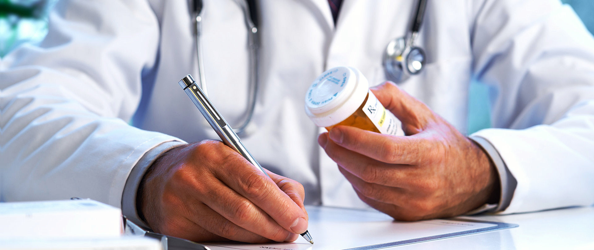 doctor writing prescription while holding bottle of medicine