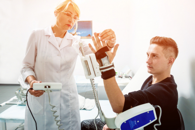 female medical professional checking the hand of young man