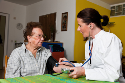 female doctor checking the blood pressure of senior woman